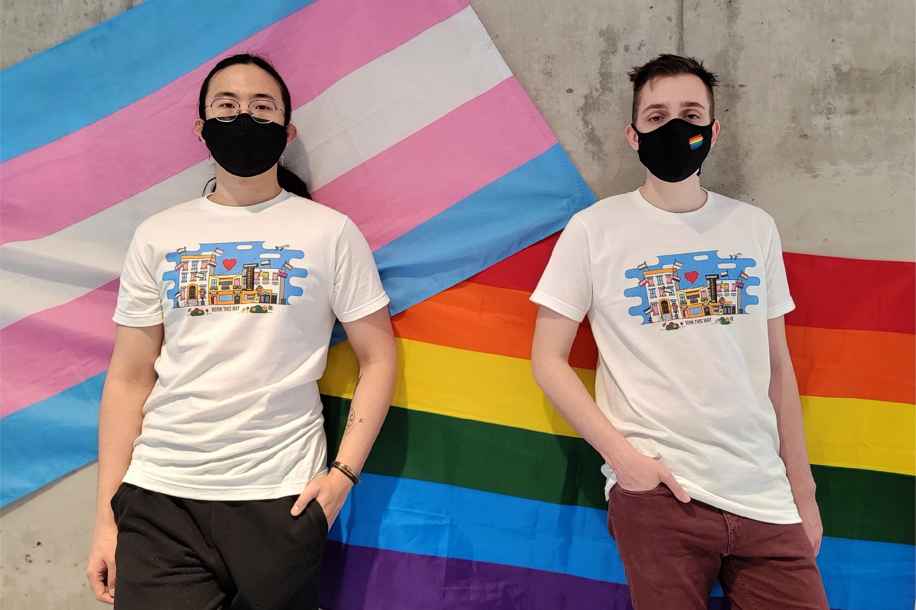 Pride 2021 tee being modelled by two students from the glow center in front of a pride flag and a transgender flag
