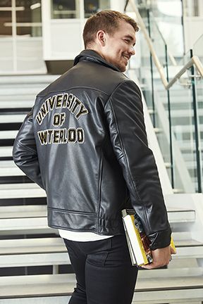 Student wearing a leather jacket with University of Waterloo in felt letters on the back