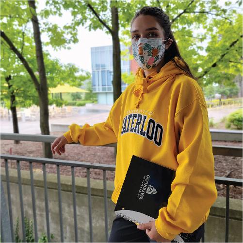 Student on campus wearing UWaterloo hoodie holding UWaterloo notebook