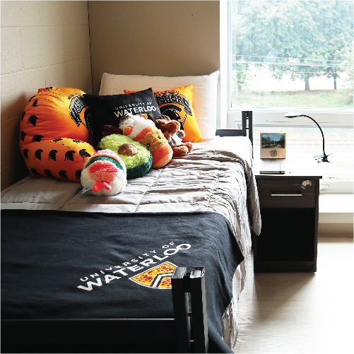 Dorm room bed decorated with UWaterloo items