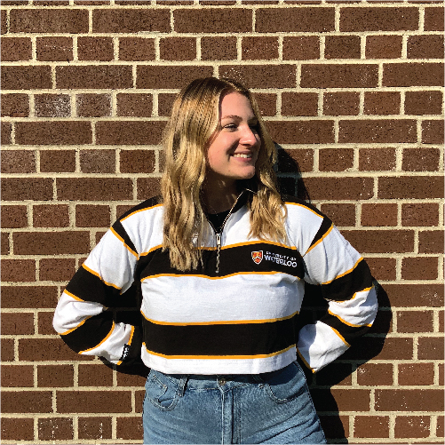Student wearing Canadian-made rugby crop top posing in front of brick wall