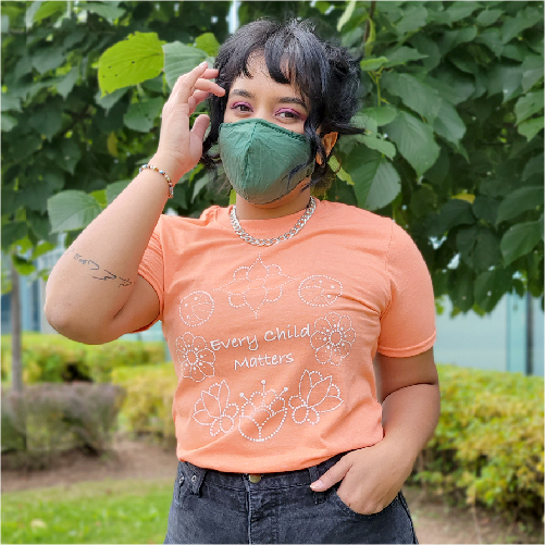 Student on campus wearing Every Child Matters orange tee