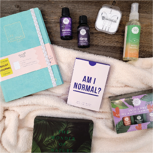 Journal, essential oils, Am I Normal cards and headphones laid on top a fluffy blanket