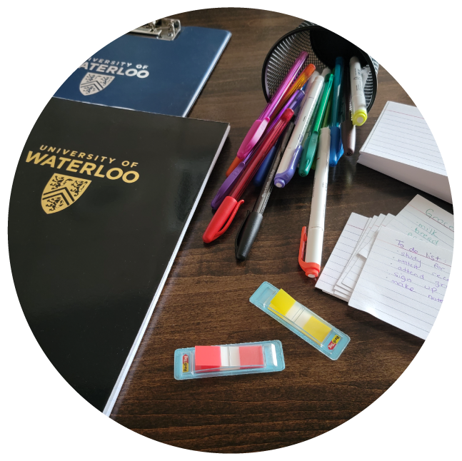 Pens and UWaterloo notebooks displayed on a desk