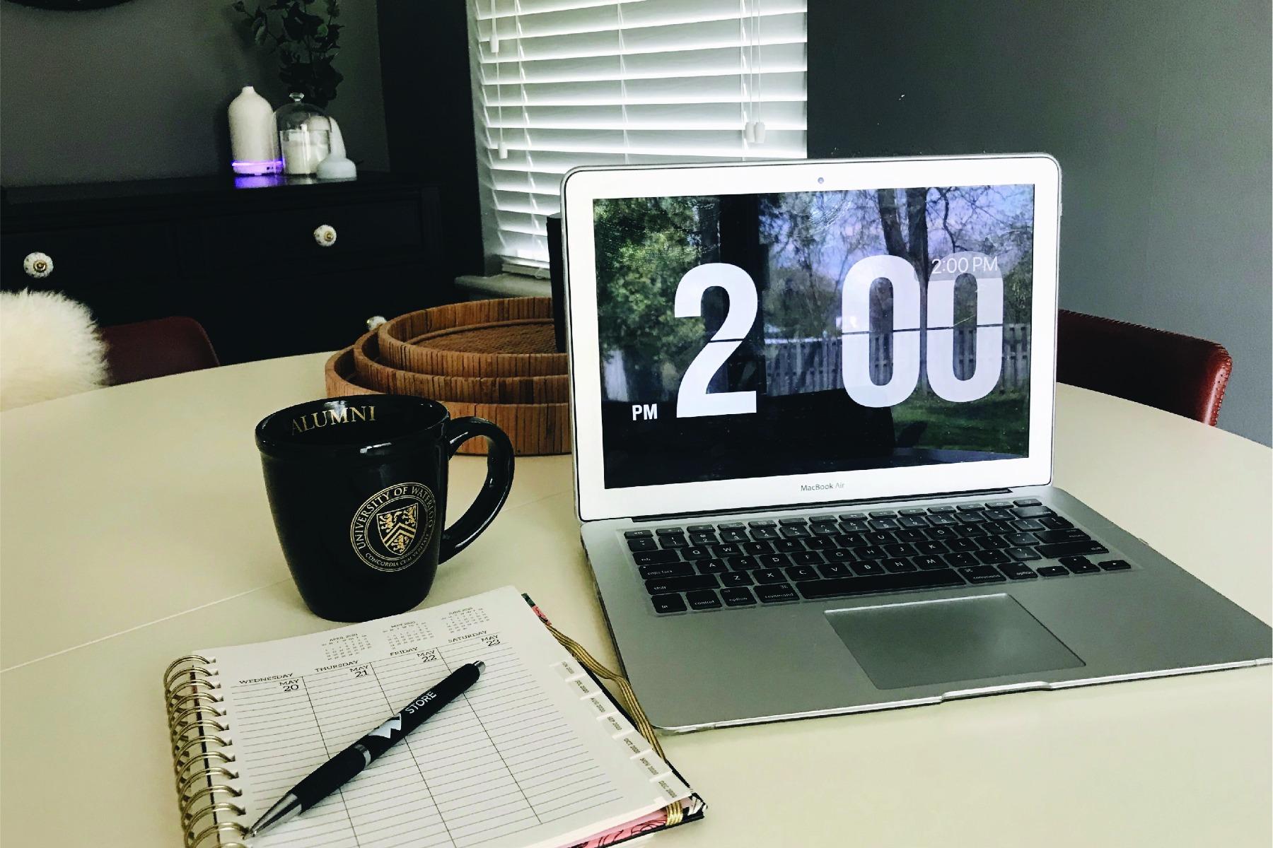 Laptop, UWaterloo Alumni mug and notebook on table